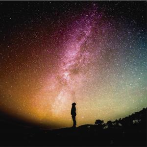 Hombre mirando al cosmos como carátula de un capítulo de A Ciencia Cierta: El destino final del Universo