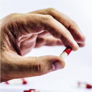 Mano sujetando una cápsula con placebo como carátula de un capítulo de A Ciencia Cierta