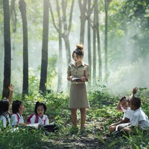 Profesora enseñando a sus alumnos en un bosque como portada del programa de A Ciencia Cierta: Enseñanza basada en la evidencia.