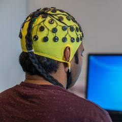 """Fotografía de la aplicación de un casco de electroencefalogramas sobre la cabeza de un hombre de espaldas como carátula del episodio """"Leer el cerebro"""" de La Ciencia que Viene"""