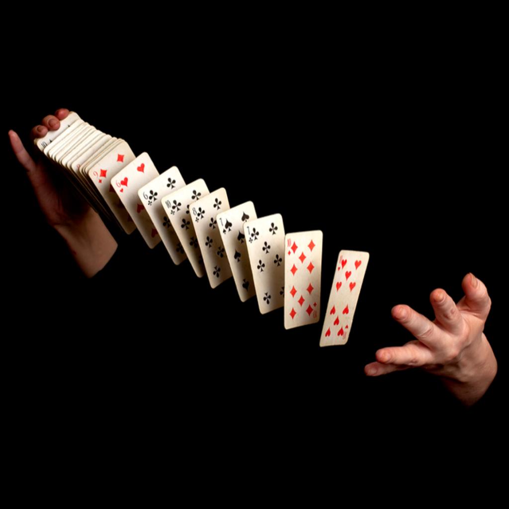 Foto de stock de un mago oculto en la oscuridad lanzando las cartas de una mano a la otra como portada del episodio de A Ciencia Cierta: Magia y Neurociencia
